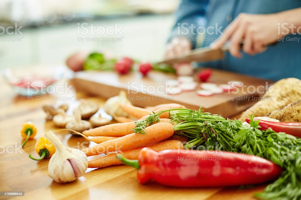 Various vegetables on table with woman chopping radish in backgr stock photo
