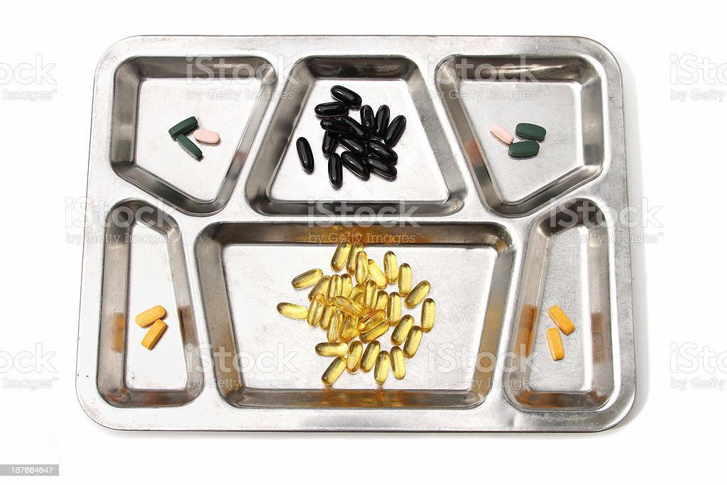 Various vitamin and nutrient pills on metal dinner tray stock photo
