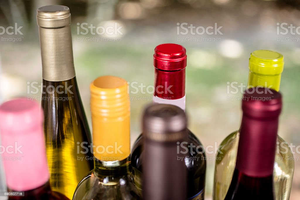 Wine tasting event. Various wine bottles on outdoor patio table. Wine...