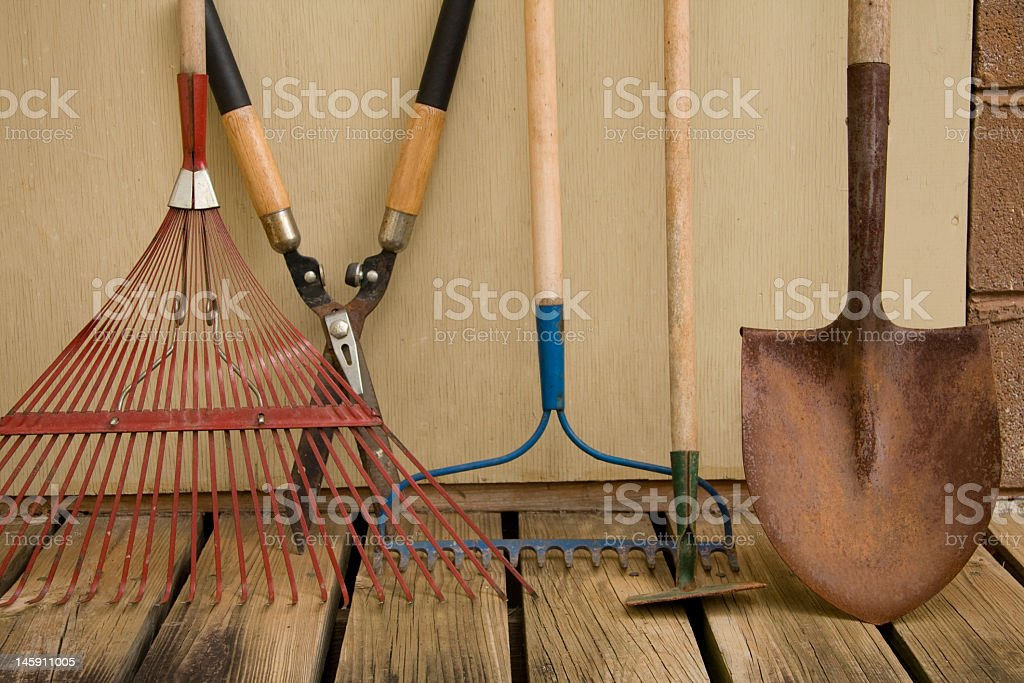 Various yard tools leaning up against wall stock photo