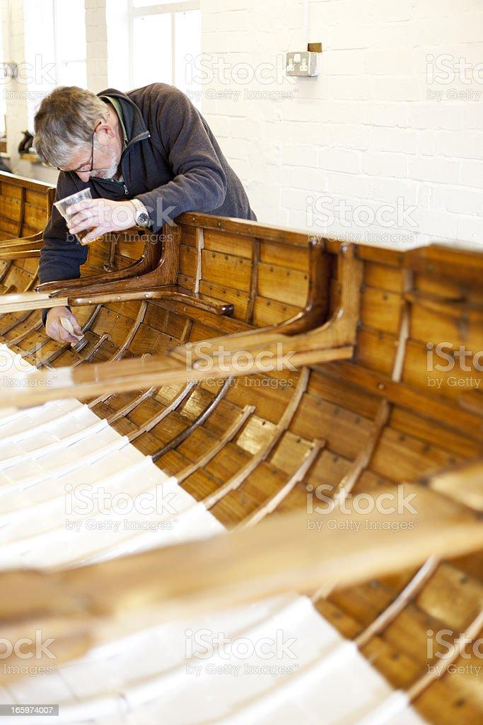 Varnishing a gig boat stock photo
