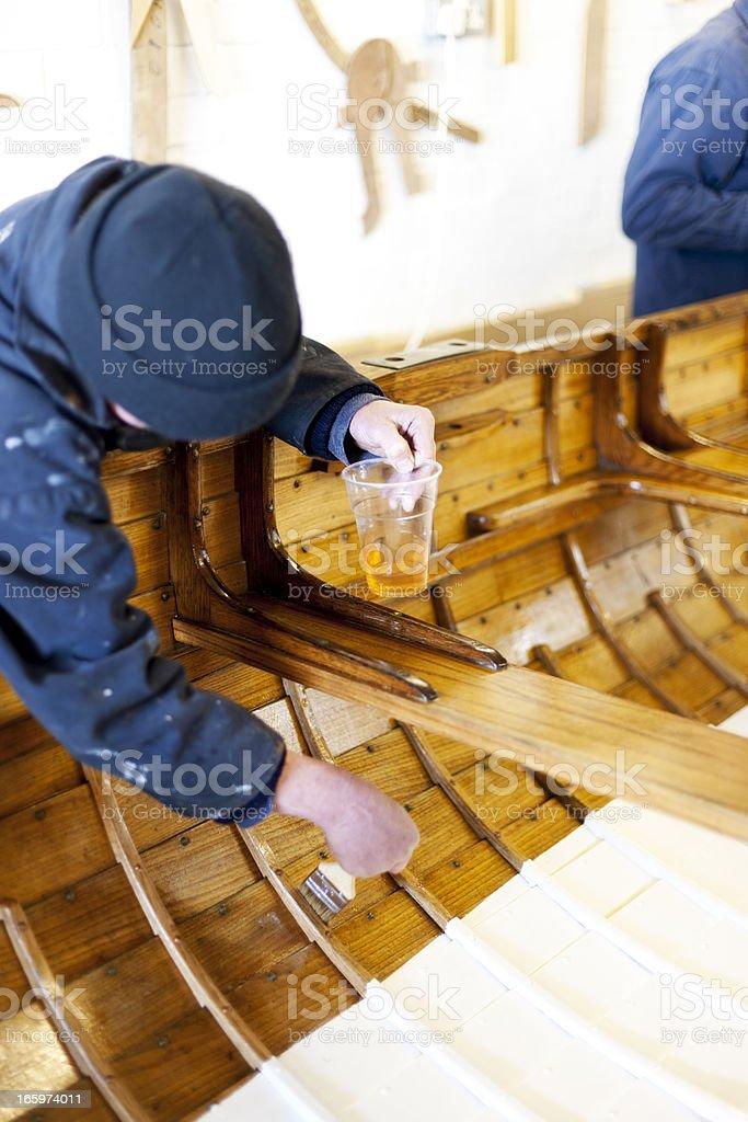Varnishing a gig boat royalty-free stock photo