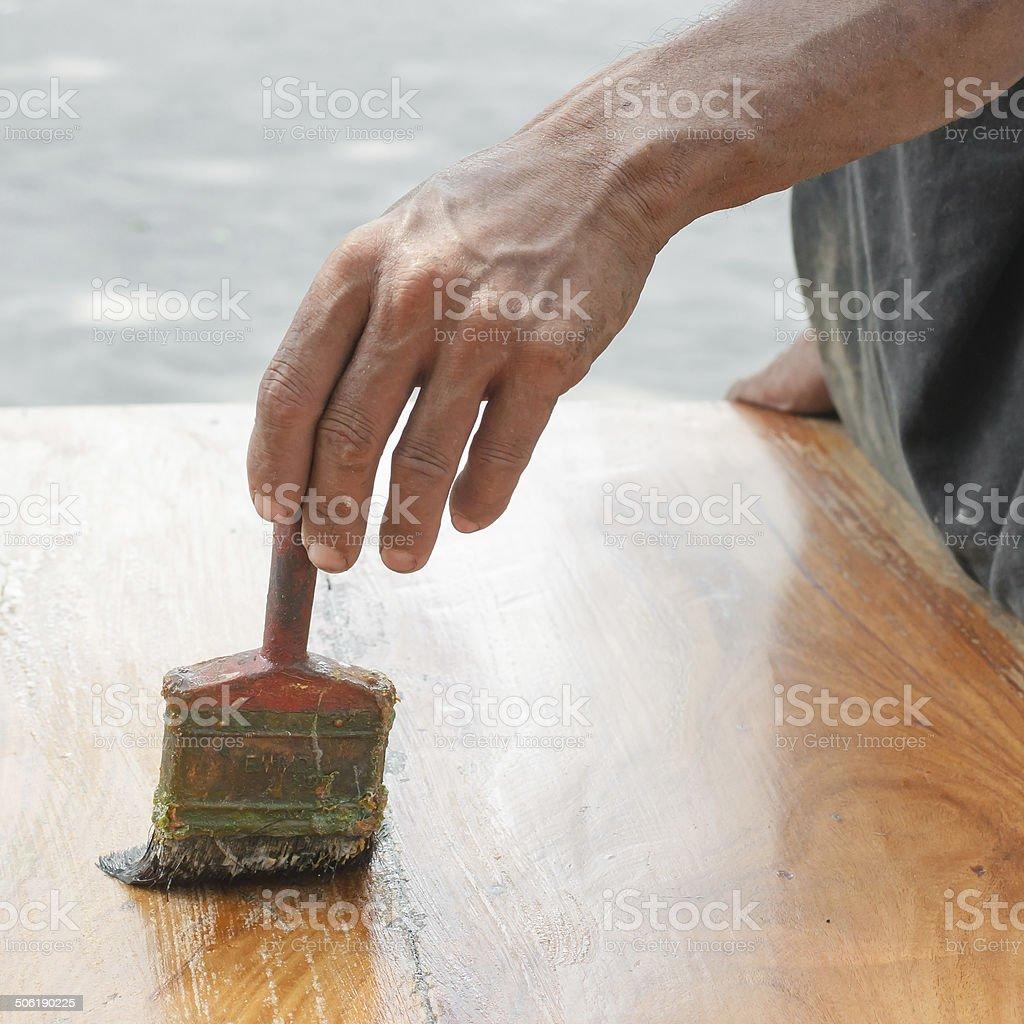 Varnishing antique wooden table  using paintbrush stock photo