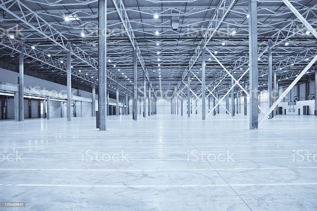 Vast empty warehouse with white floors and silver beams stock photo