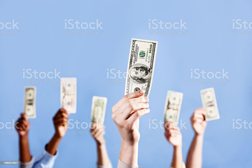 I've got the money! Many hands holding up US dollars royalty-free stock photo