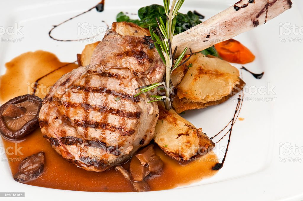 Veal chop on plate served with vegetables stock photo