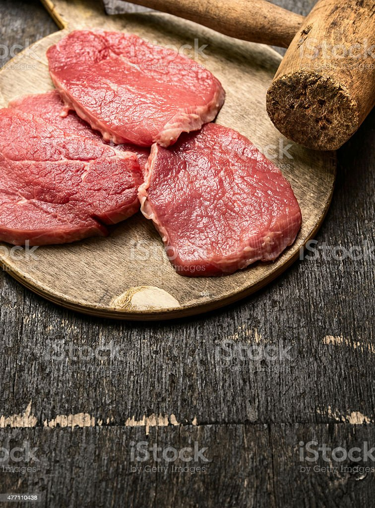 Veal schnitzel preparation  with old meat hammer stock photo