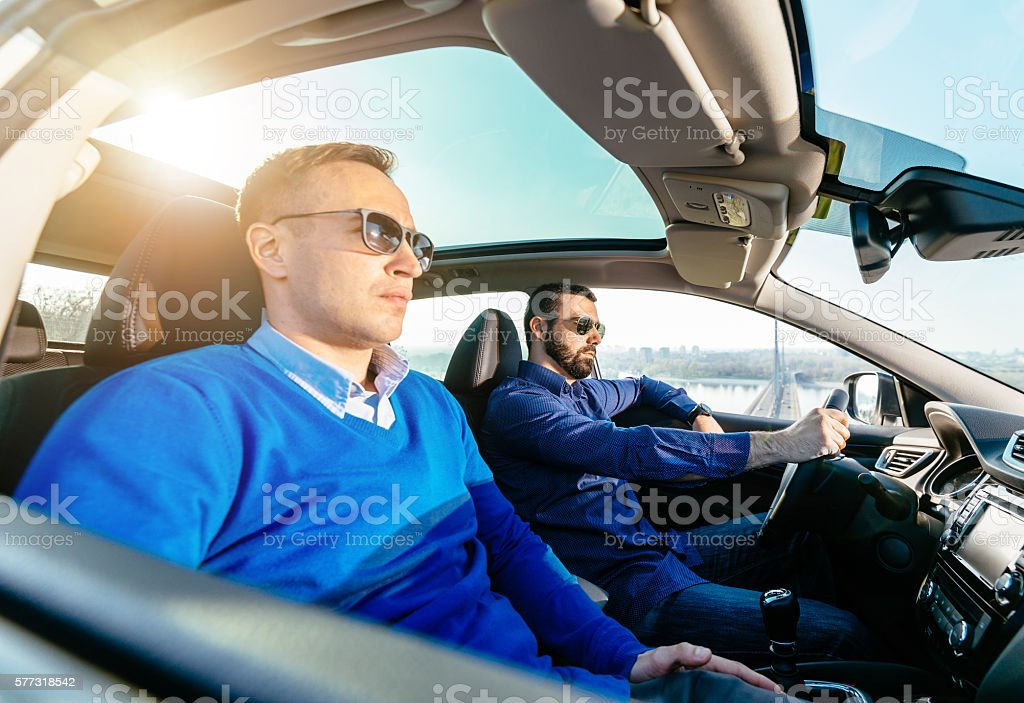 Vechile interior with two handsome men going for ride stock photo