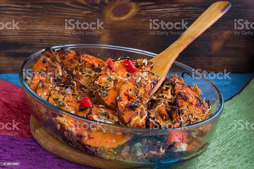 Vegan baked dish in glass pan, pumkin, vegetables, herbs, cheese stock photo