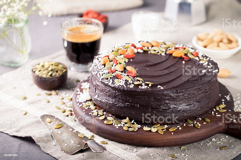 Vegan chocolate beet cake with avocado frosting, decorated nuts, seeds stock photo