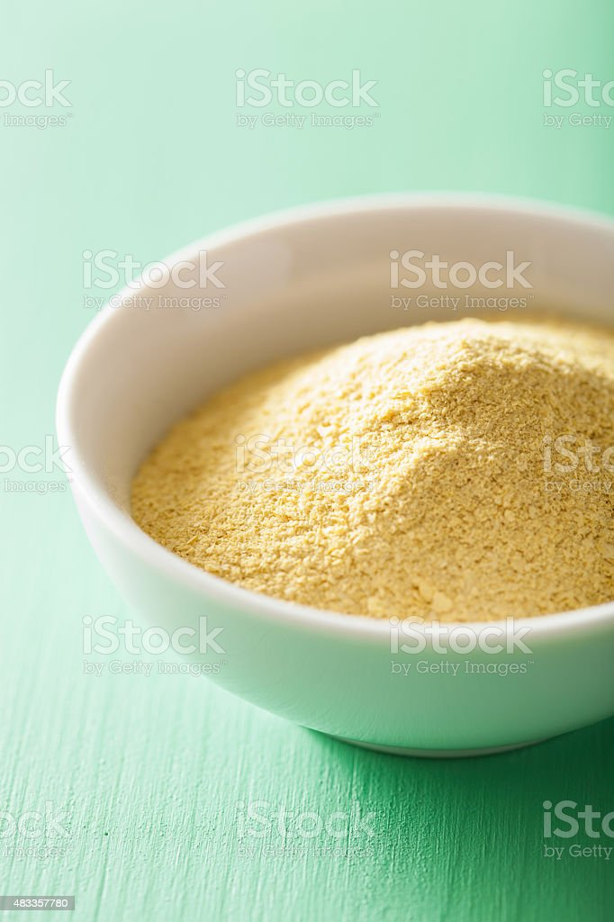 vegan nutritional yeast flakes in bowl stock photo