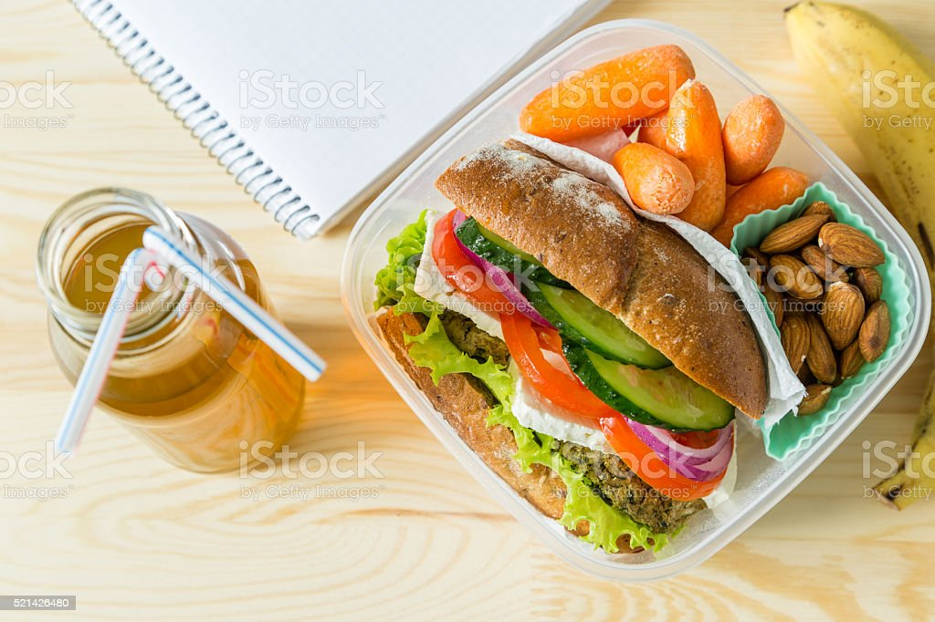 Vegan sandwich in lunch box with carrots and nuts stock photo