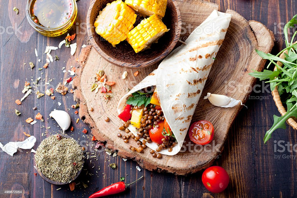 Vegan tortilla wrap, roll with grilled vegetabes, lentil, corn cob. stock photo
