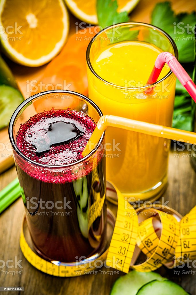 Vegetable juice: Beet and orange with straws and measuring tape stock photo