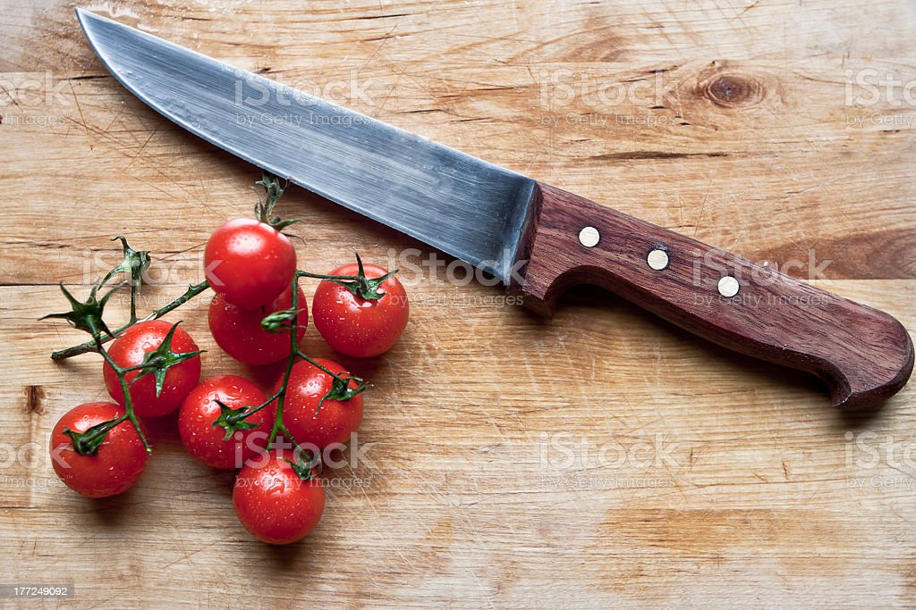 Vegetable knife next to eight red tomatoes on the vine stock photo