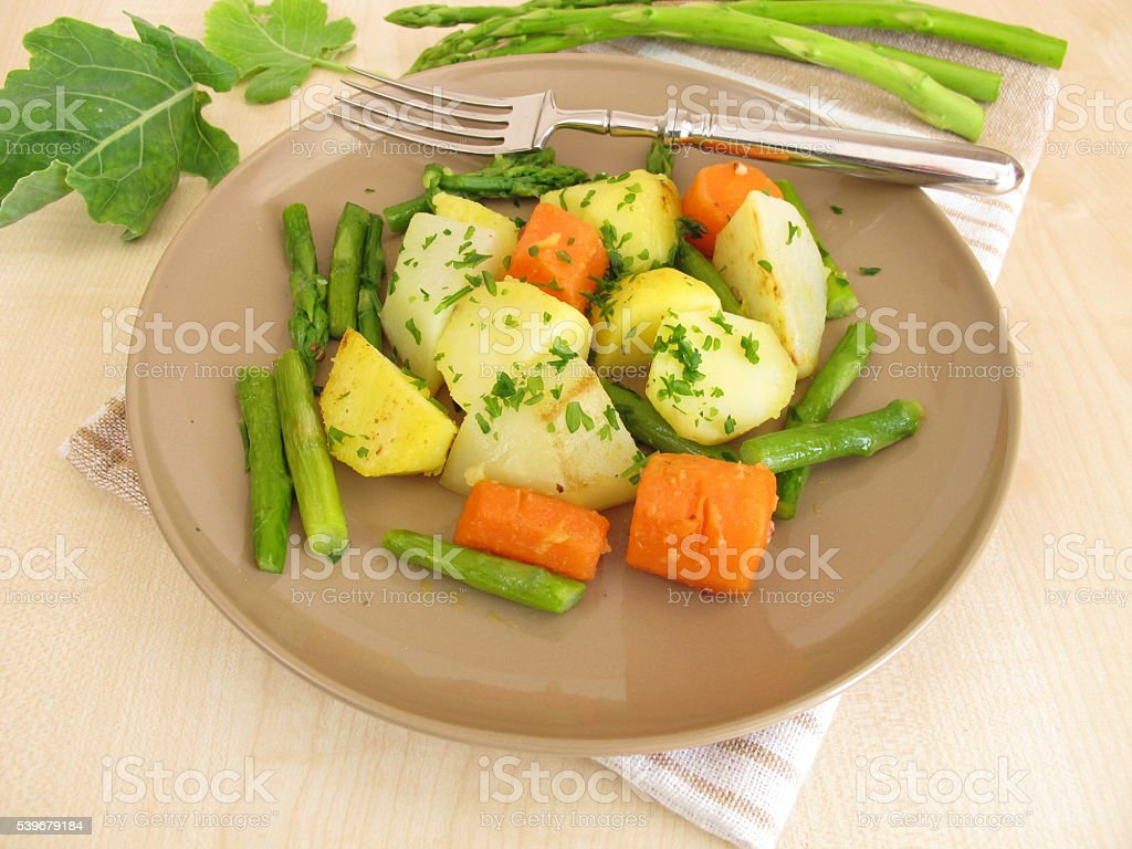 Vegetable pan with green asparagus, carrots, potatoes and german turnip stock photo