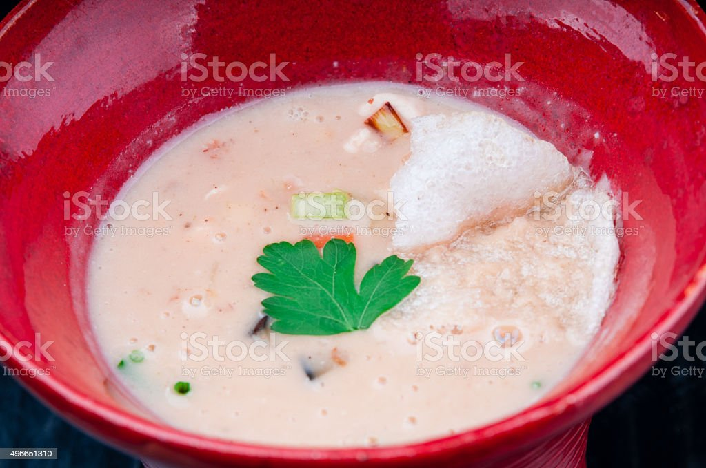 Vegetable potage served in a red cup on a table stock photo
