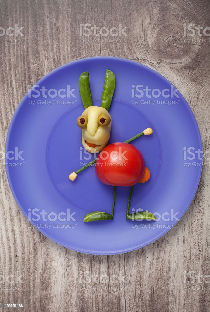 Vegetable rabbit on blue plate on wooden background stock photo