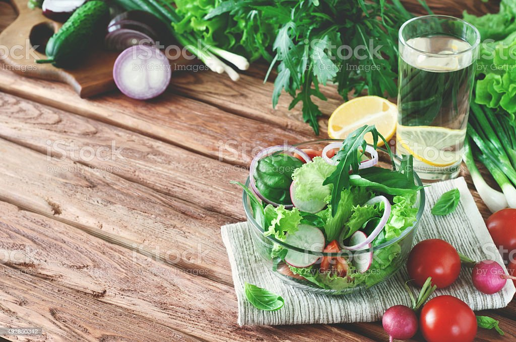 Vegetable salad with a glass of water on the table stock photo