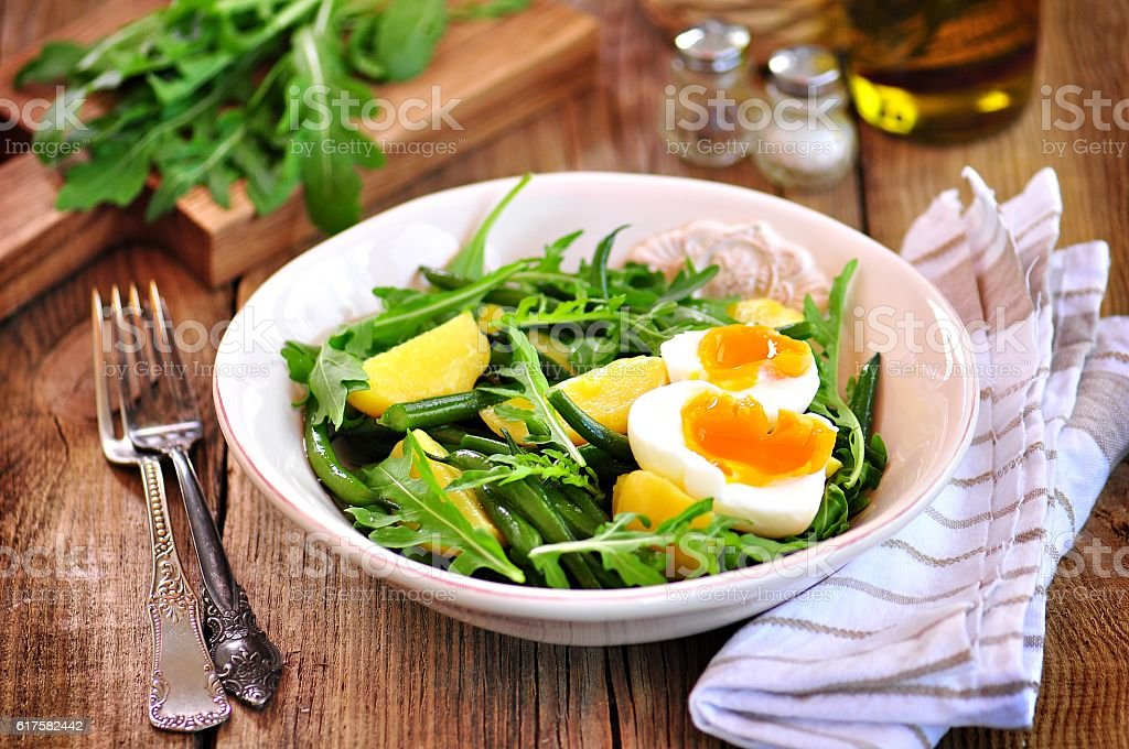Vegetable salad with green beans, potatoes, arugula, eggs, olive oil stock photo