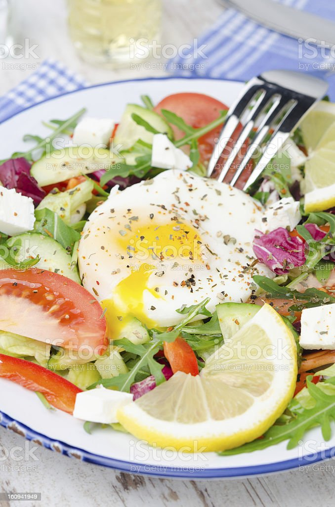 Vegetable salad with poached egg on a plate, vertical royalty-free stock photo