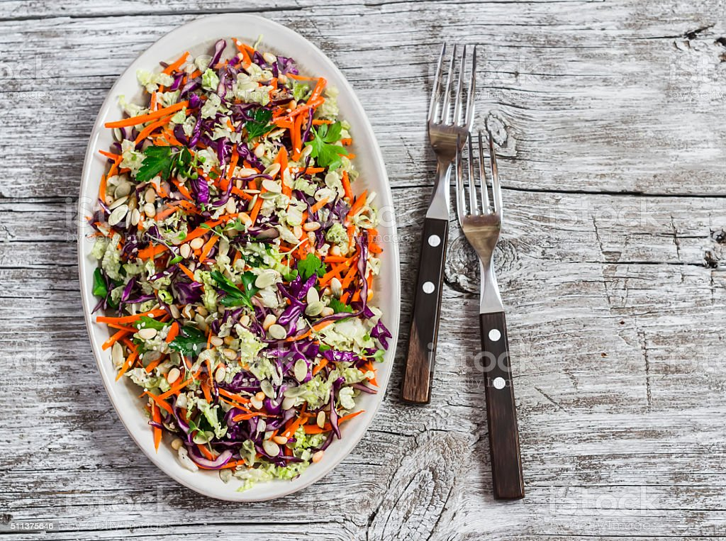 Vegetable salad with red cabbage, carrots, peppers, herbs and seeds stock photo