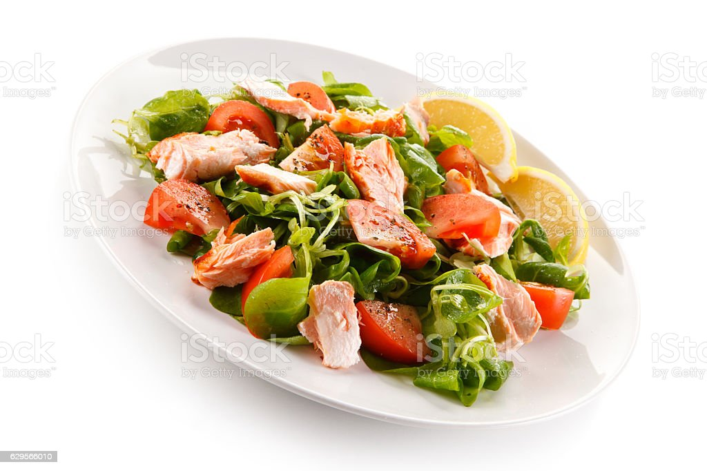 Vegetable salad with salmon on white background stock photo