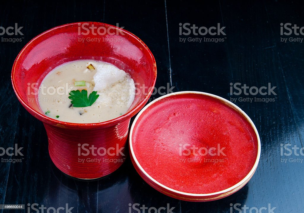 Vegetable soup served in a red cup on a table stock photo