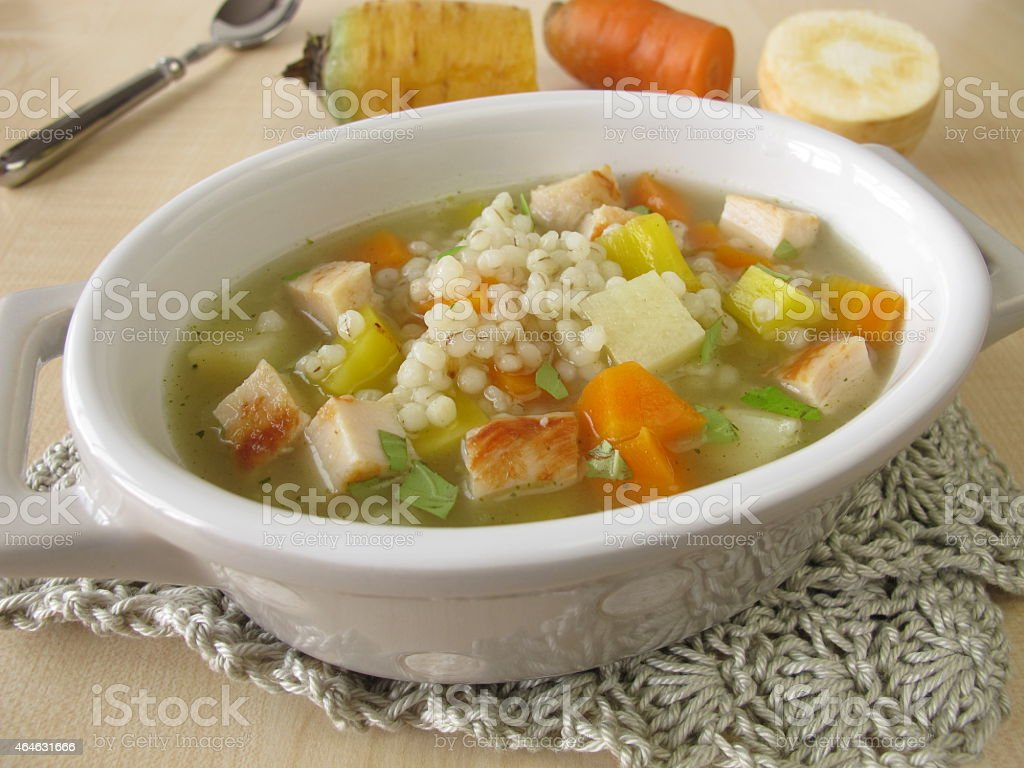 Vegetable soup with pearl barley and chicken stock photo