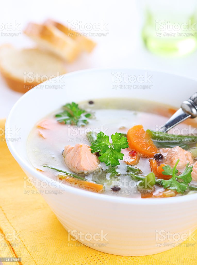Vegetable soup with salmon in white bowl stock photo