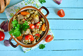 Vegetable stew with meat and barley on a blue background