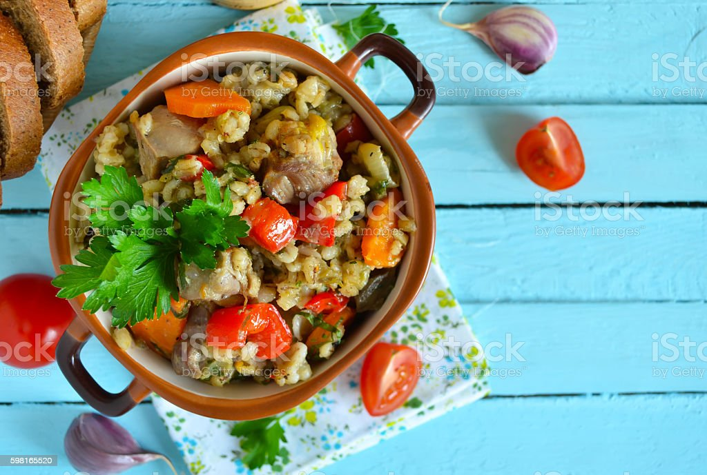 Vegetable stew with meat and barley on a blue background stock photo