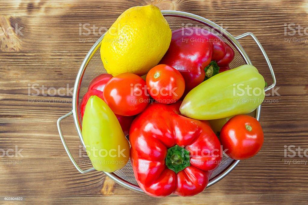 Vegetable still life of peppers, tomatoes, lemon in bowl stock photo