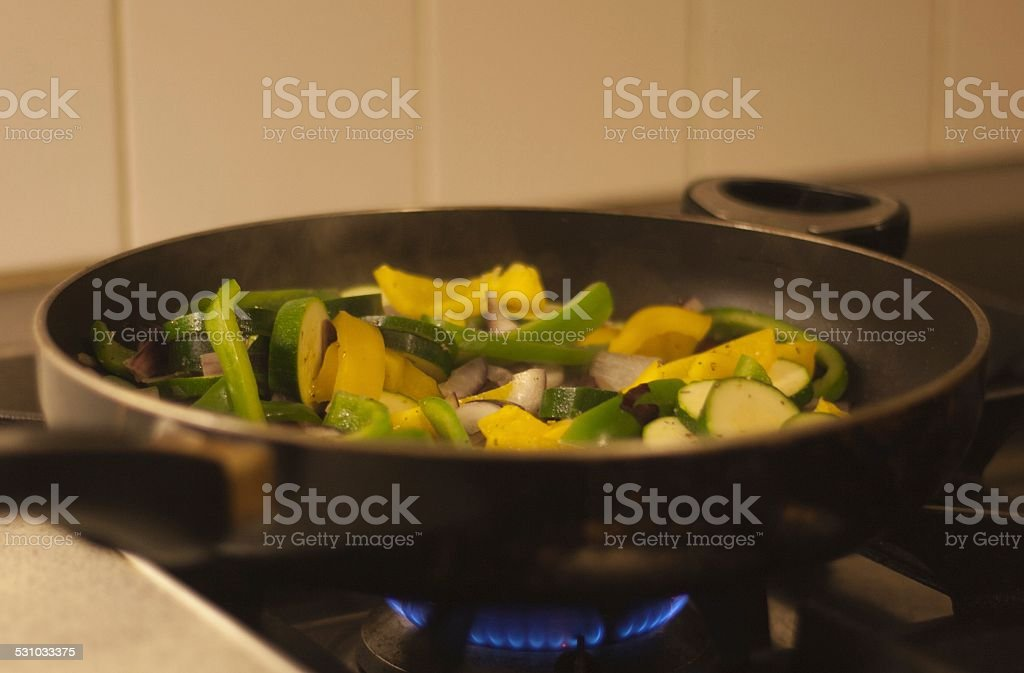 vegetable stir fry cooking on a hob stock photo