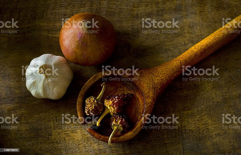 Vegetables and wooden spoon on vintage cutting board royalty-free stock photo