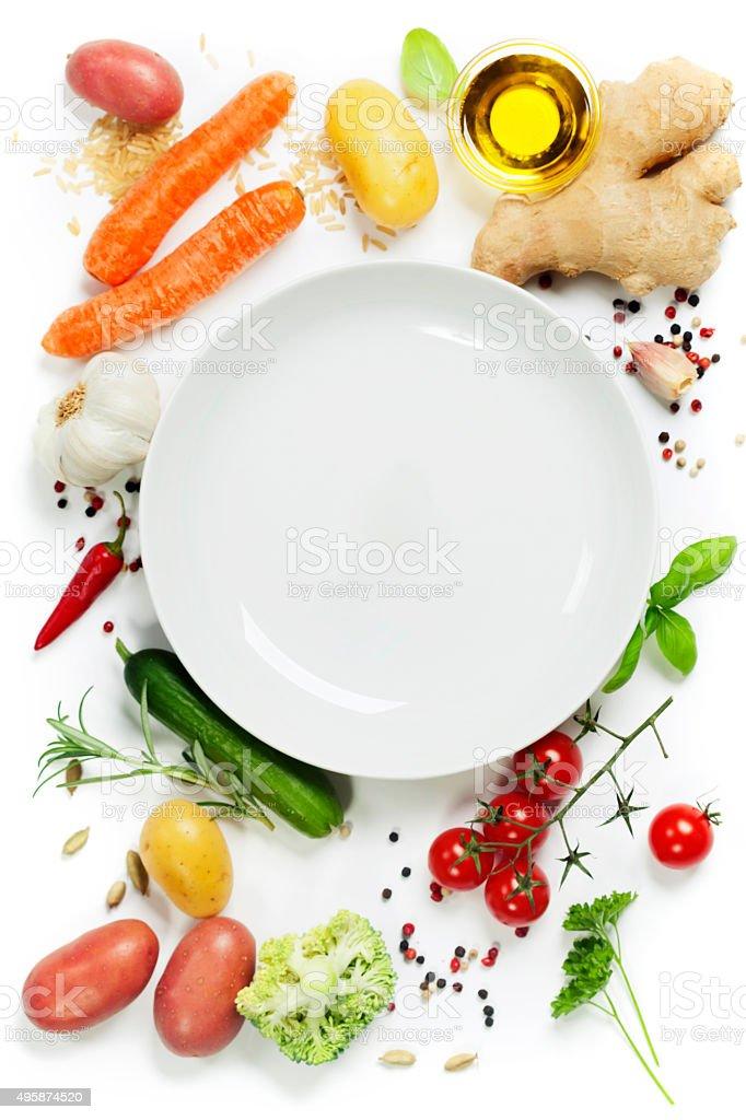 Vegetables around empty white plate stock photo