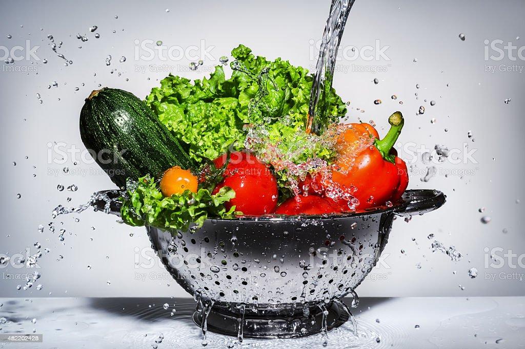 vegetables in a colander under running water stock photo