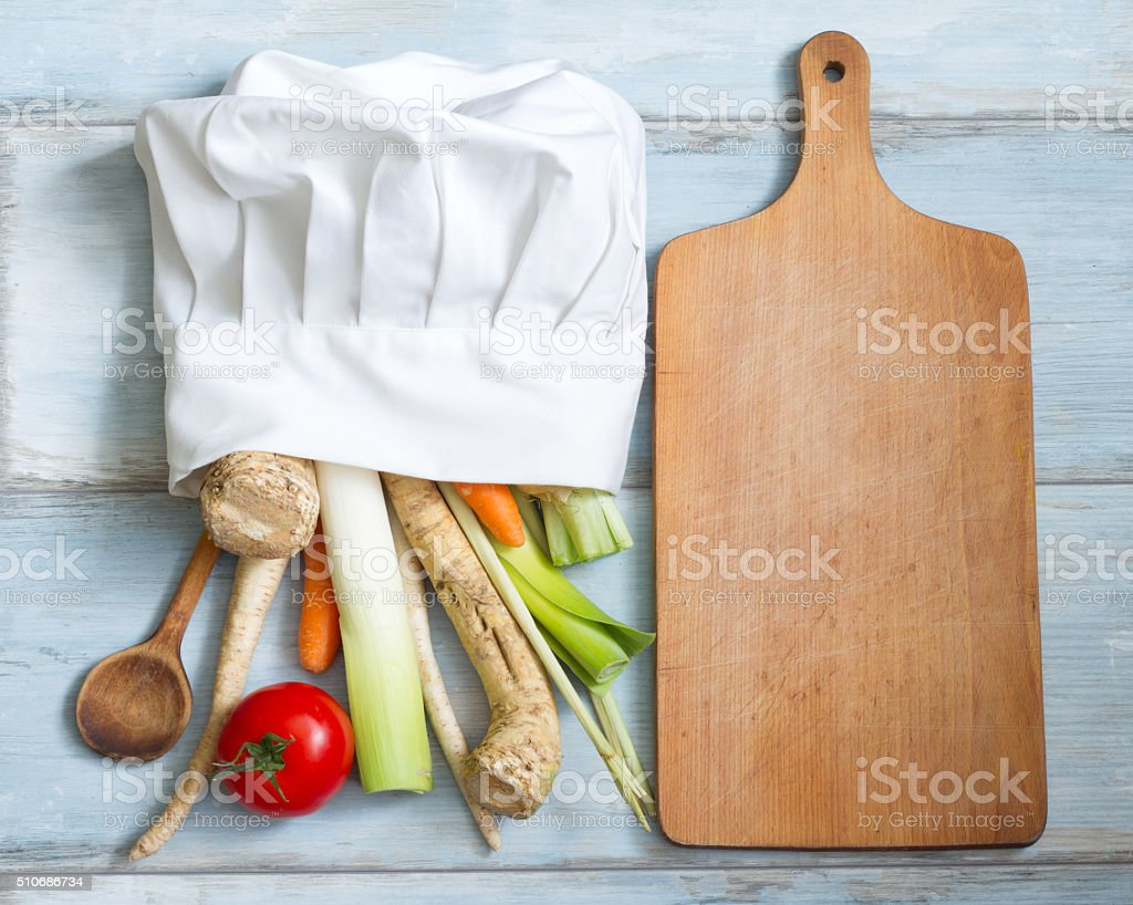 Vegetables in chef's hat and empty cutting board stock photo