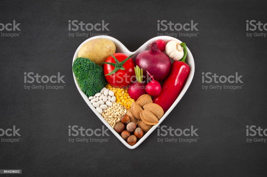 Vegetables in Heart Shaped Bowl on Blackboard stock photo