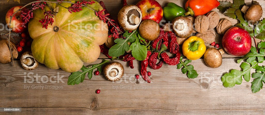 Vegetables, nuts, berries and  fruits over old wooden table. stock photo