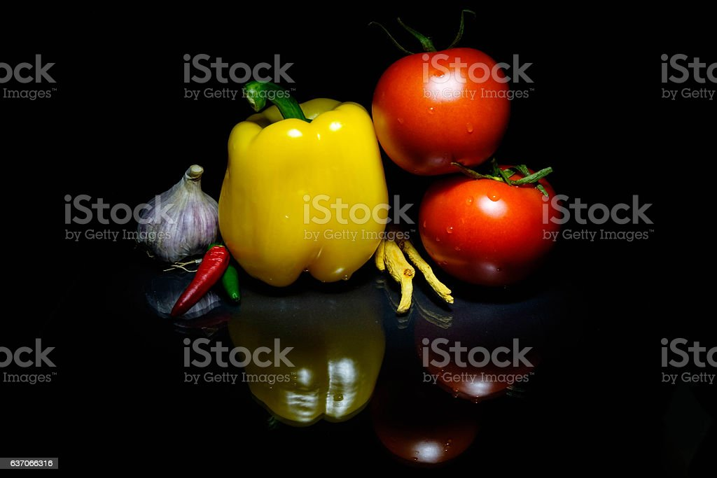 Vegetables on a board and a dark background tomatoes peppers stock photo