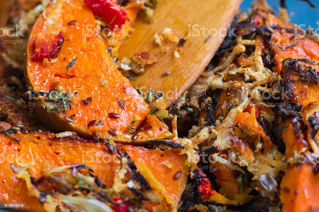 Vegetarian baked dish close-up with pumkin, vegetables, herbs, cheese stock photo