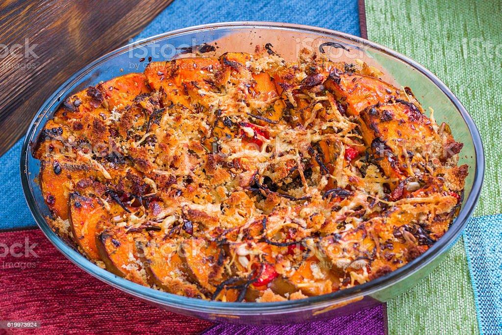 Vegetarian baked dish of orange pumkin, vegetables, herbs, cheese stock photo