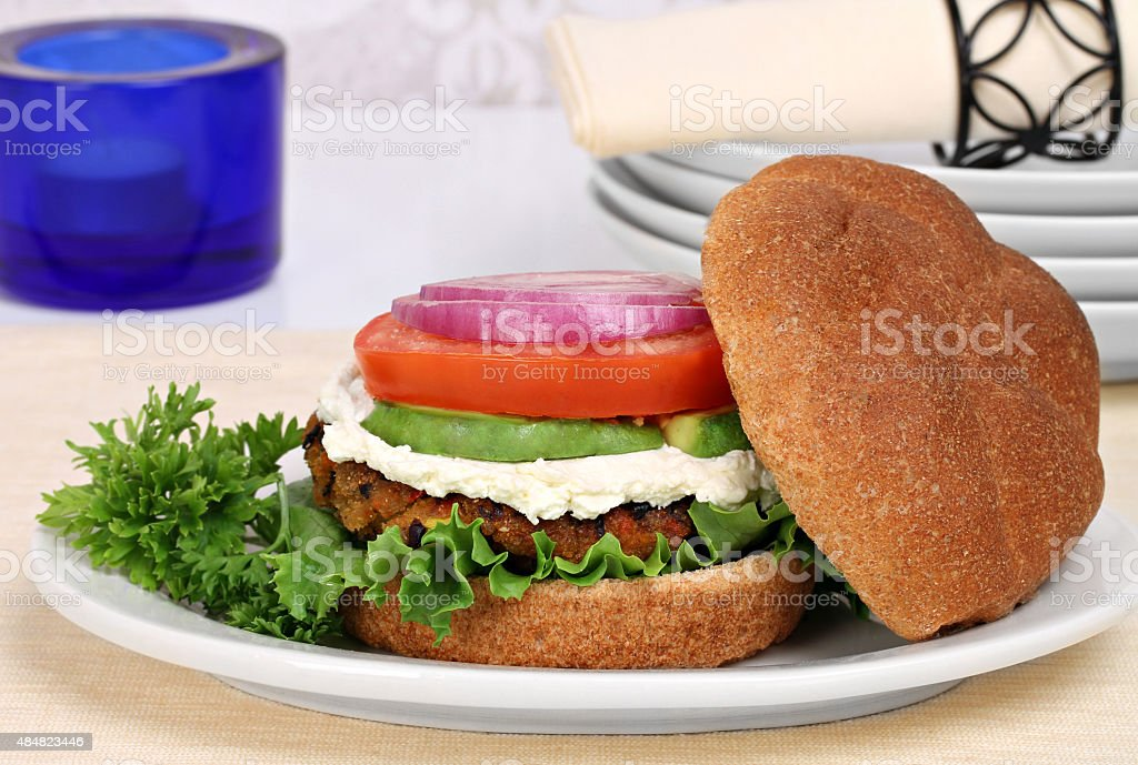 Vegetarian black bean burger on a whole wheat roll. stock photo