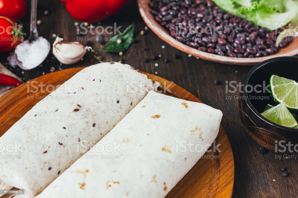 Vegetarian burrito on wooden board over black table surrounded by ingredients. stock photo