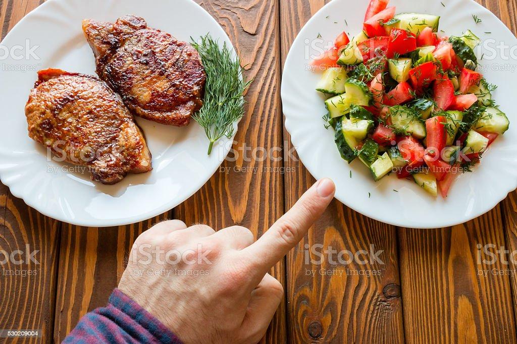 vegetarian chooses salad instead of fried meat stock photo