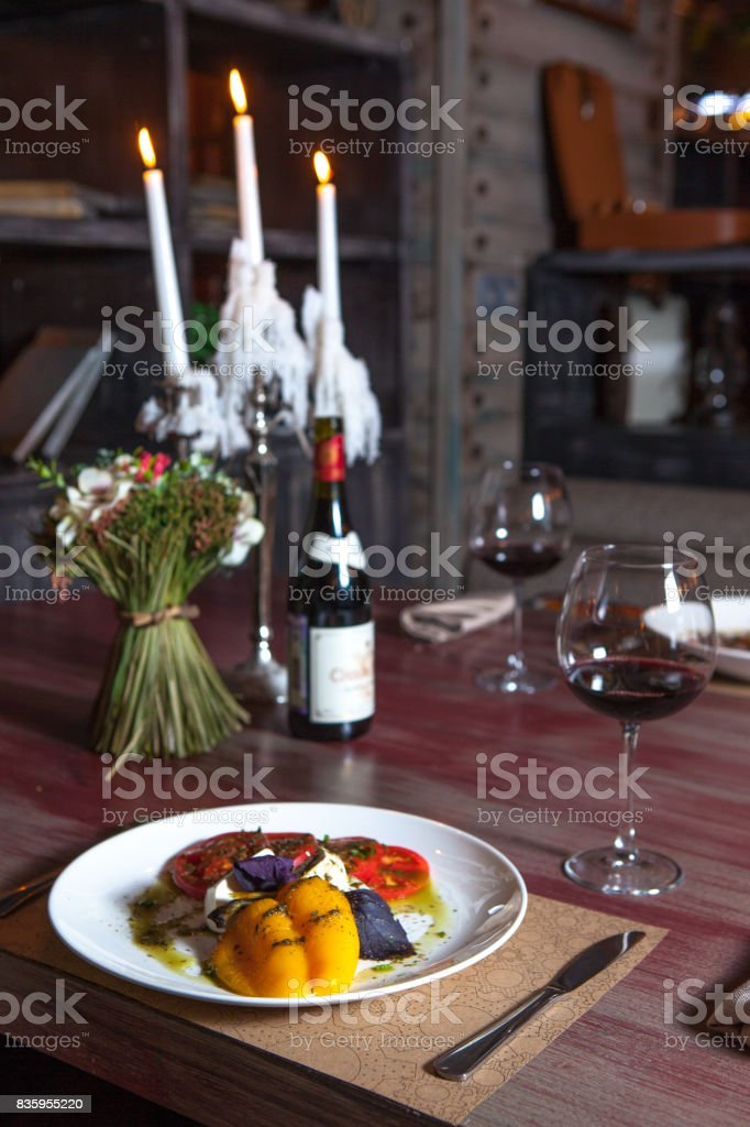 vegetarian dish in the restaurant at a table with glasses of wine stock photo