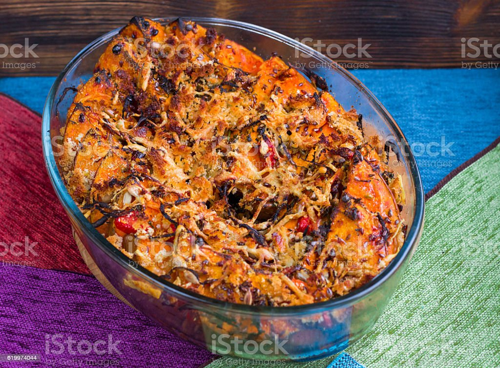Vegetarian dish of baked orange pumkin, mixed vegetables, herbs, cheese stock photo