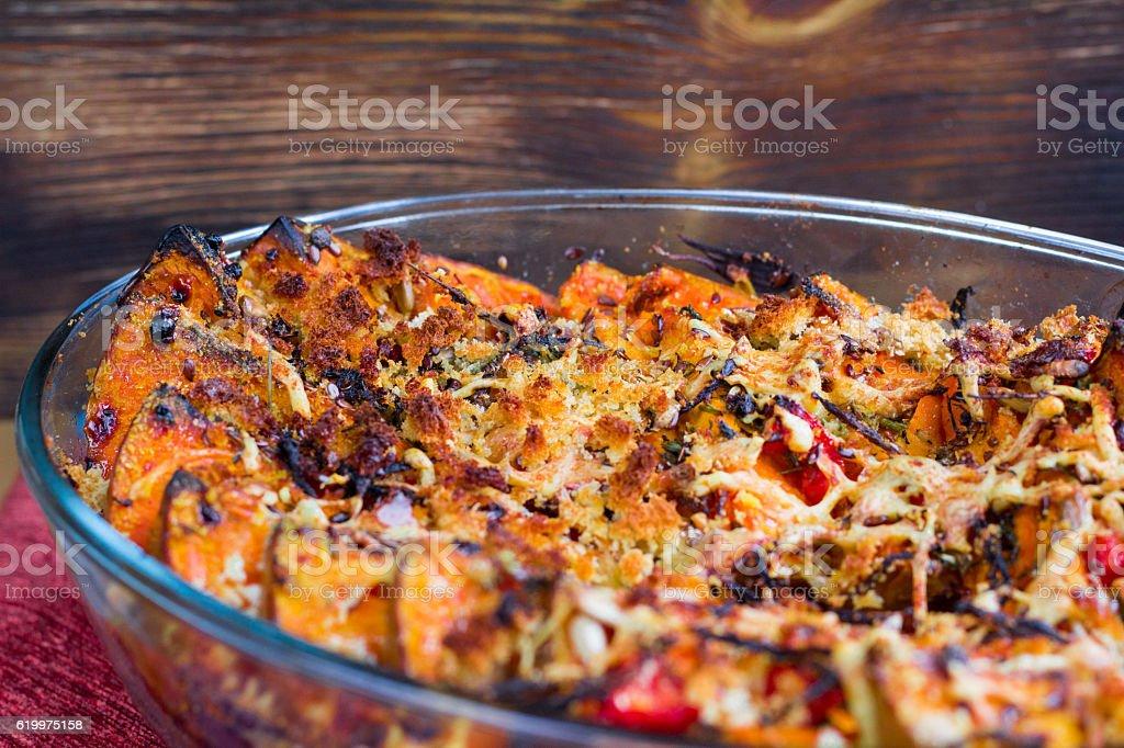 Vegetarian dish of baked pumkin, vegetables, herbs, cheese stock photo