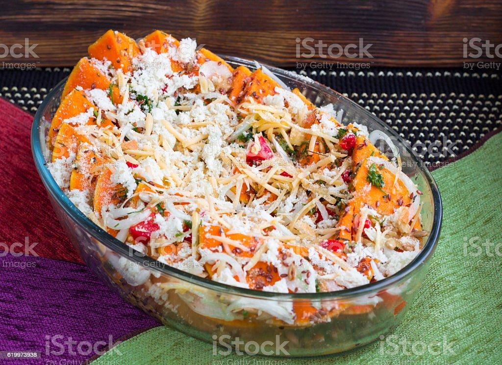 Vegetarian dish of orange pumkin, vegetables, herbs and cheese stock photo